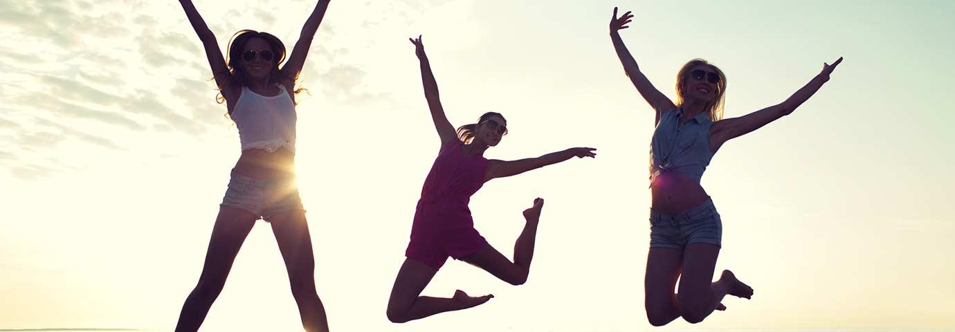 Glückliche Gruppe springt in die Luft vor Freude