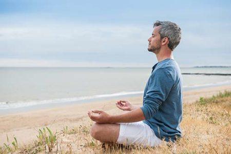 Mann meditiert am Strand