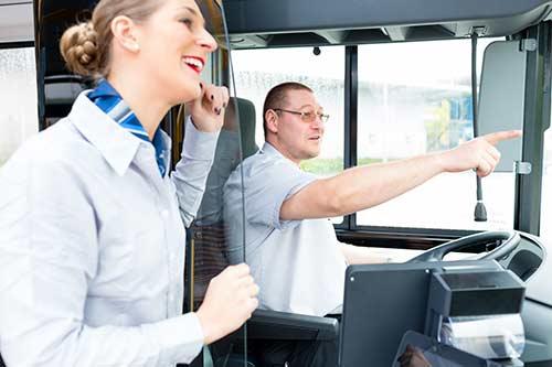 Busfahrer und Ausbilder schauen aus dem Bus