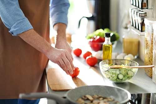 Mann schneidet eine Tomate für gesundes Essen