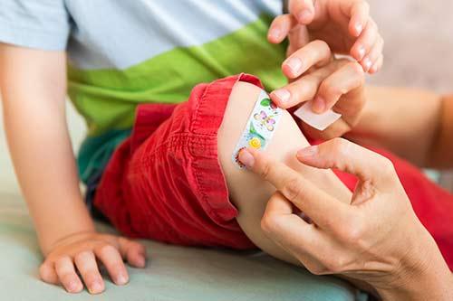 Kind bekommt ein Pflaster auf das Knie