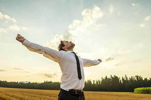 Mann streckt seine Arme in den Himmel
