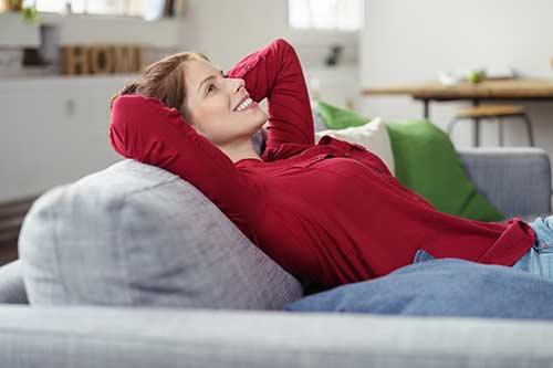 Frau entspannt mit PME auf dem Sofa