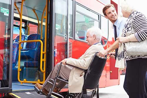 Busfahrer hilft Rollstuhlfahrerin in den Bus