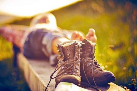 Wanderer liegt auf einer Bank neben seinen Stiefeln