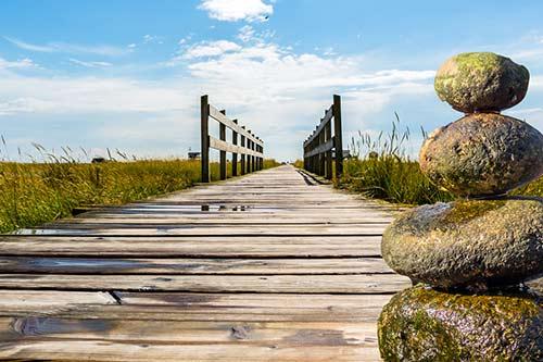 Steg zum Strand und Steine in Balance