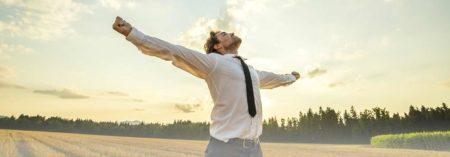 Mann streckt die Arme in die Luft und geniesst die Natur